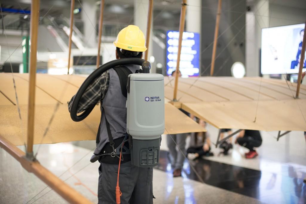 清潔員用可攜式吸塵裝備清除機翼上的塵埃。