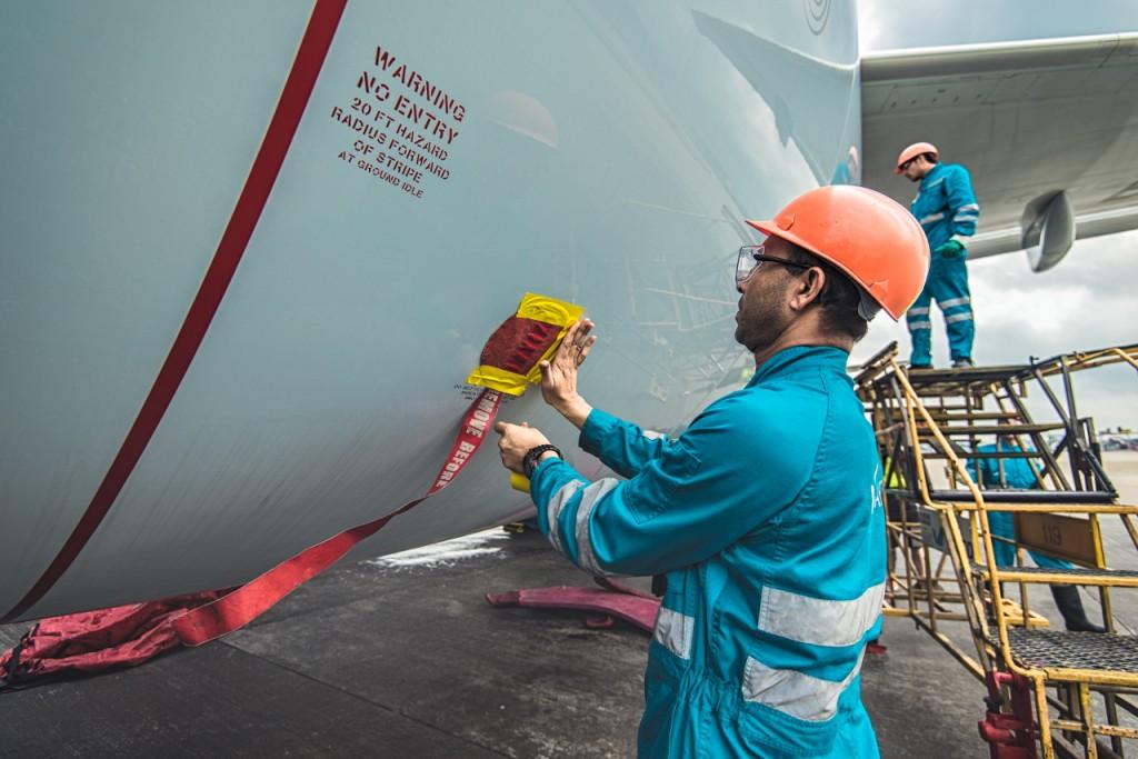 清潔員用防水膠布把飛機不可沾水的部件封好,並貼上印着「REMOVE BEFORE FLIGHT」的紅色標示帶。