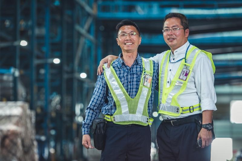 鄭煒財(左)和凌立(右)多年來在空運貨站並肩作戰,縱然行業經歷種種變遷,仍不改他們對工作的熱誠。
