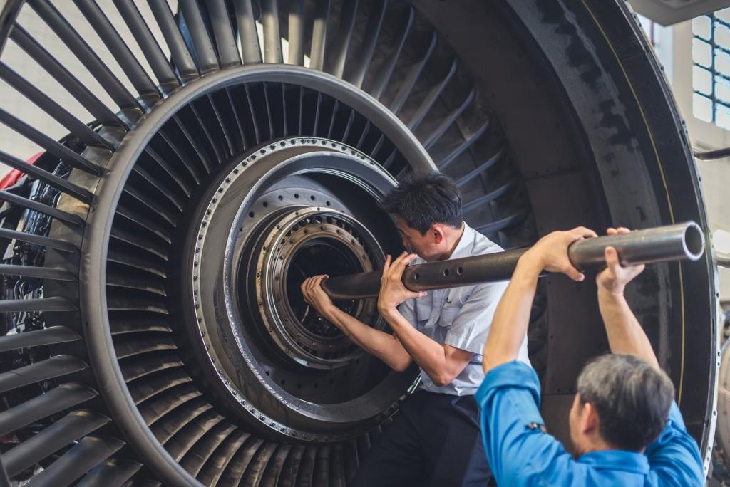 麥德光(左)和同事合力將引擎分拆成主要組件。